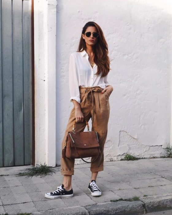 Slim long hair woman in white blouse and brown paper bag pants with black converse