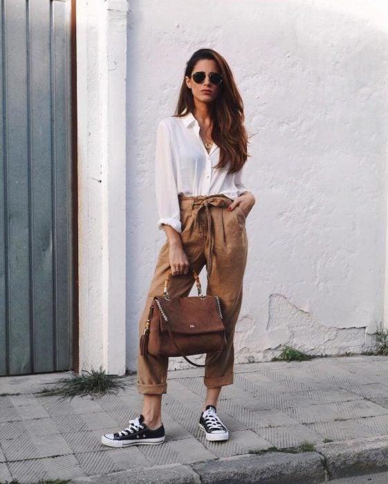 Mujer delgada de cabello largo con blusa blanca y paper bag pants cafés con converse negros