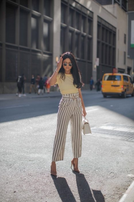 Black and long hair brunette woman in yellow blouse with striped paper bag pants