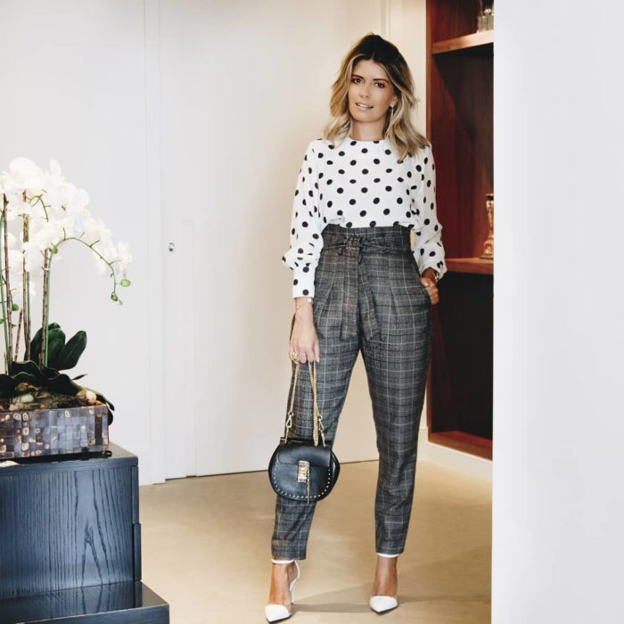 Standing blonde woman posing in white circle blouse and plaid paper bag pants