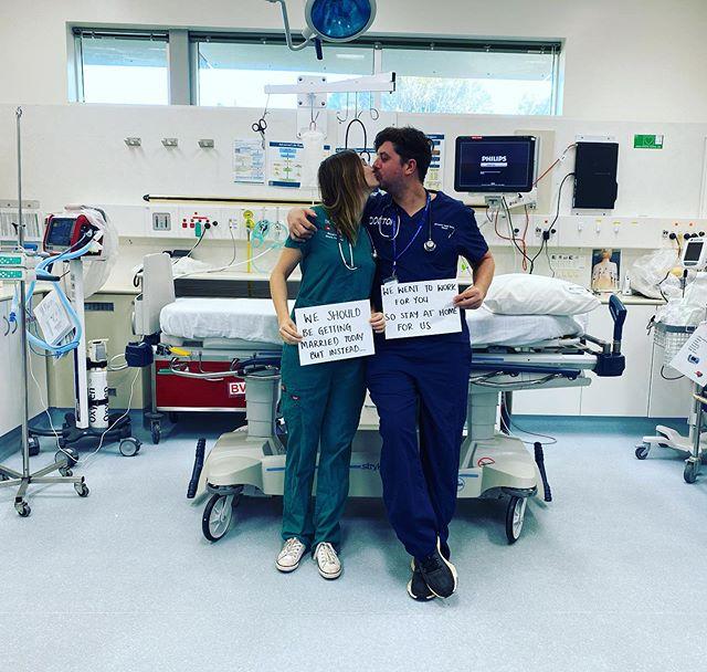 Pareja de doctores sosteniendo un cartel y besándose mientras están en un quirofano