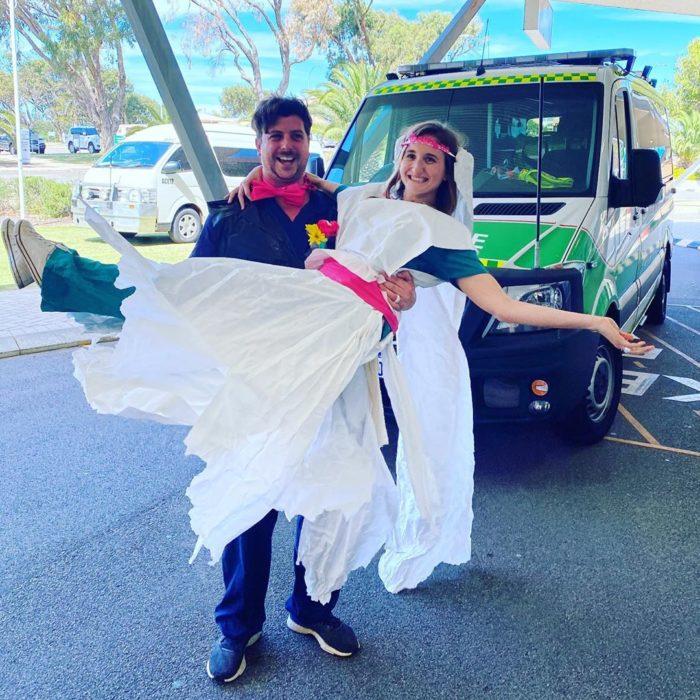 Chico sosteniendo a una chica en brazos mientras está usando un vestido de novia hecho con papel y bolsas de basura
