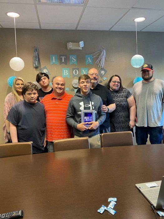 Familia reunida frente a un computador sonriendo por la sesión de adopción de un chico de 17 años