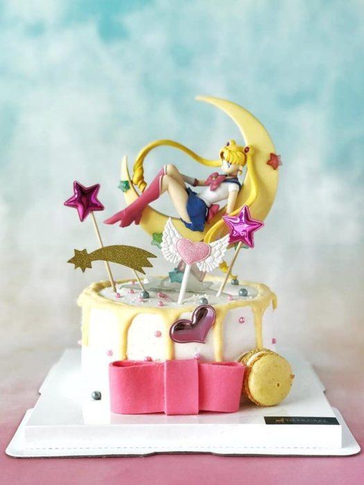 Pastel de Sailor Moon con base de fondant blnaca, una figurilla de Serena en sobre una luna y demás detalles
