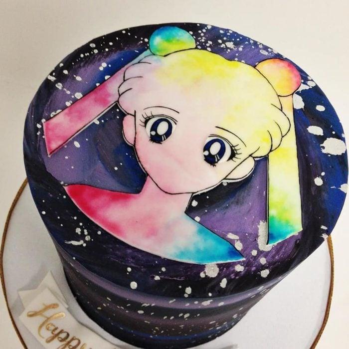 Pastel de Sailor Moon en base de fondant negra, y el rostro de Serena en blanco y tonalidades de arcoiris