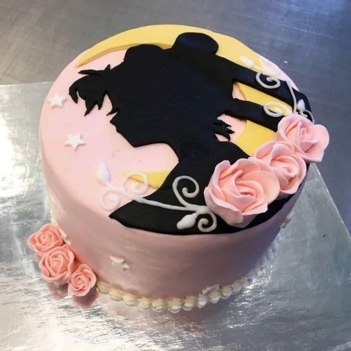 Pastel de Sailor Moon de la silueta del rostro de Serena y algunas rosas de betún decorando alrededor