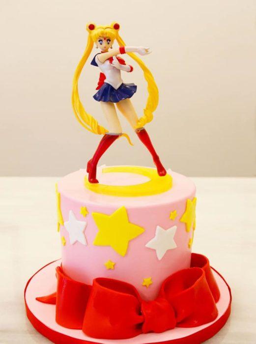 Pastel de Sailor Moon con una figurilla de juguete de Serena y fondant rosa