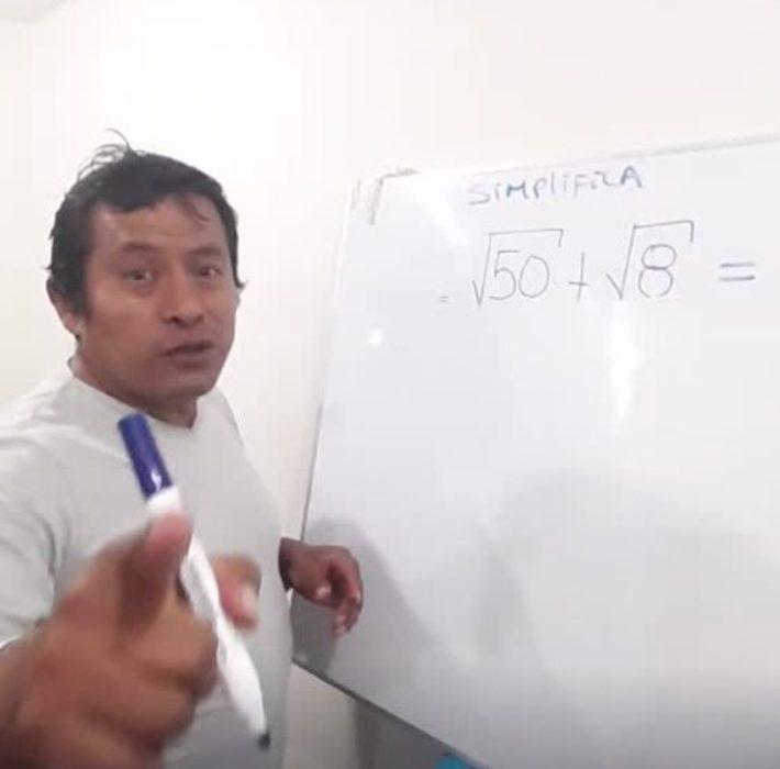 Fidel Medina explicando matemáticas en una pizarra blanca, usando plumones azules