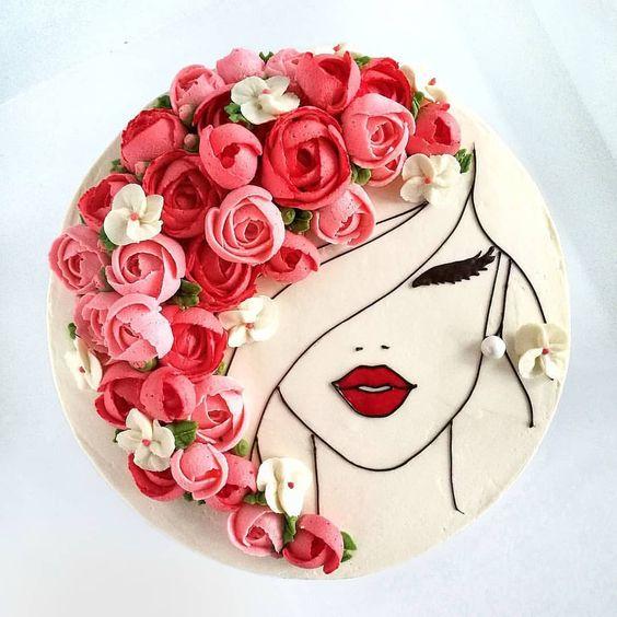 Pastel con betún blanco decorado con flores en betún rosa y rojo