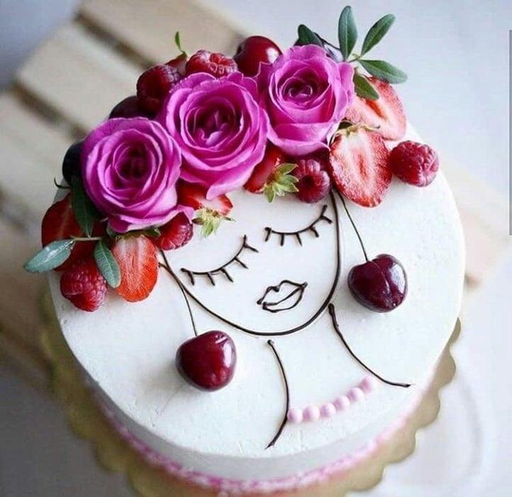 Pastel de un piso con betún blanco decorado con cerezas, fresas y rosas naturales