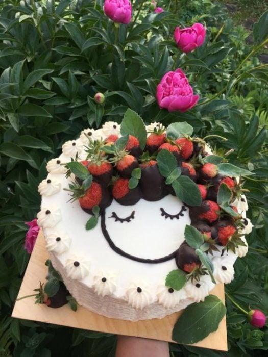 Pastel de vainilla decorado con fresas con chocolate como si fueran una cabellera larga