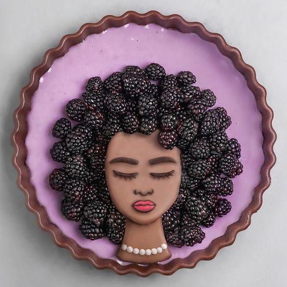 Tarta de zarzamora con queso crema decorada con fondat en forma de rostro de mujer con cabellera rizada de moras