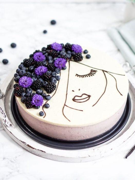 Pastel con betún en color blanco decorado con frutas en forma de cabellera