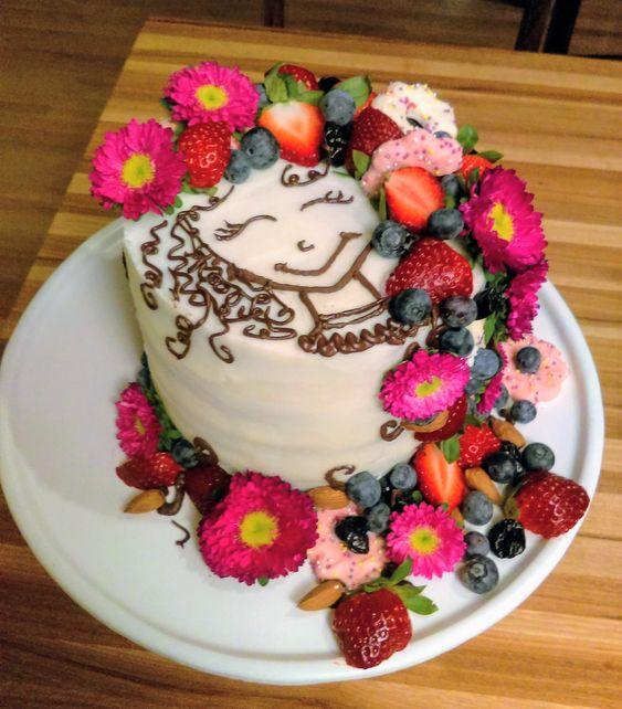Pastel de vainilla decorado con margaritas, fresas y arándanos