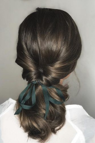 Low ponytail hairstyle with volume with green ribbon