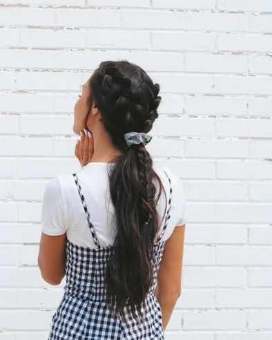 Dark-haired long-haired brunette girl in a low ponytail tied with two braids and a blue scrunchie