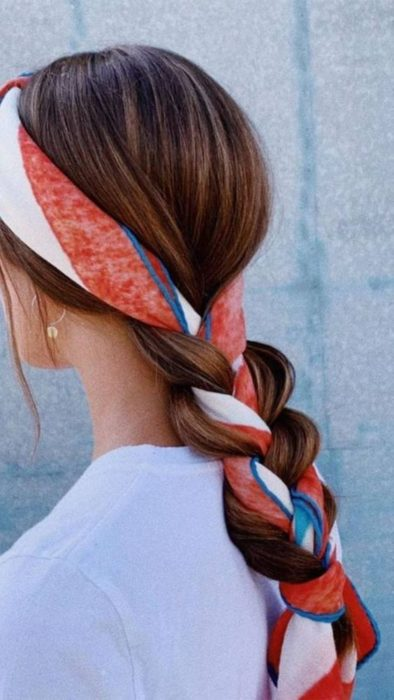 Low braid hairstyle with red, white and blue scarf