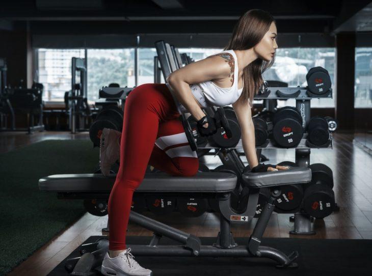 Chica realiznado carga de peso para ejercicio de brazo