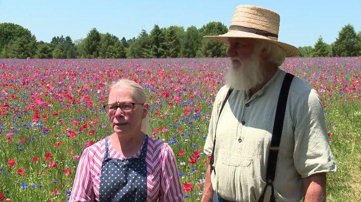 Joan Donaldson y John Van Voorhees mostrando su campo cubierto de amapolas