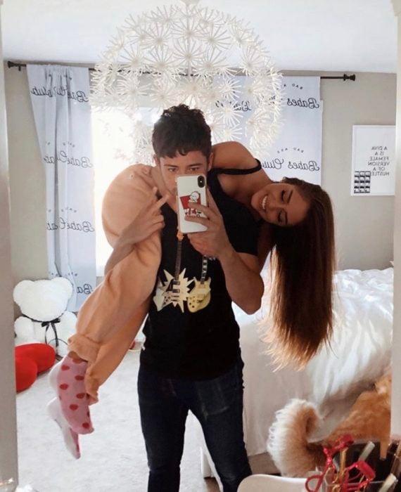 Chico carga a chica en sus hombros mientras se toman una selfie