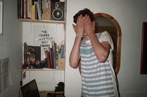 Chico con blusa blanca de rayas horizontales se tapa los ojos