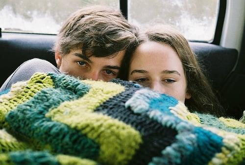 Chico y chica se tapan la mitas de la cara con una cobija tejida