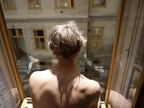 Chico rubio sin camisa mira por una ventana abierta