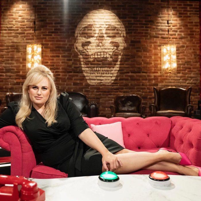 Rebel Wilson recostada en un sofá rojo llevando u vestido negro entallado