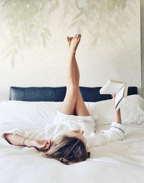 Mujer con las piernas elevadas y leyendo