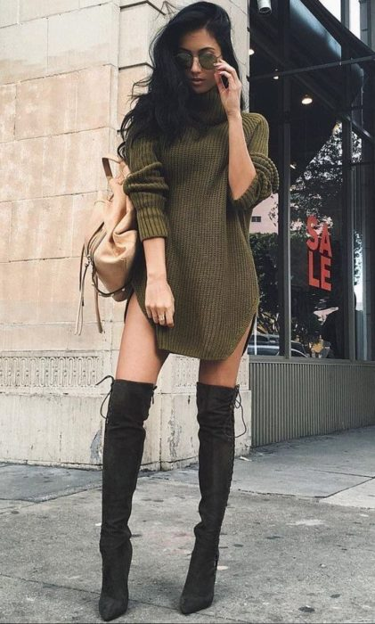 Slim girl in green long sweater with black high boots and beige backpack
