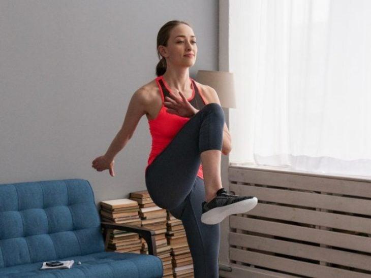 Mujer haciendo elevación de rodillas hacia el pecho