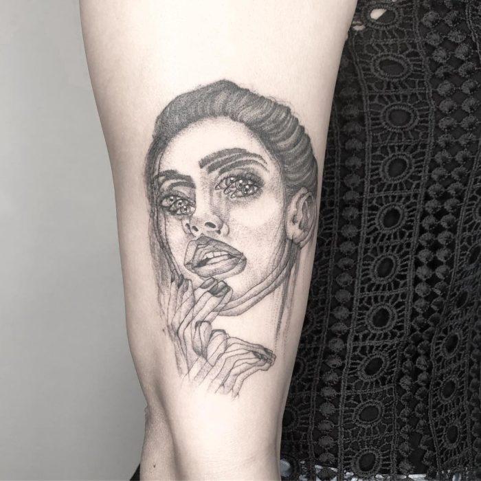 Tatuaje de ilusión óptico de una chica tocando sus labios con los dedos