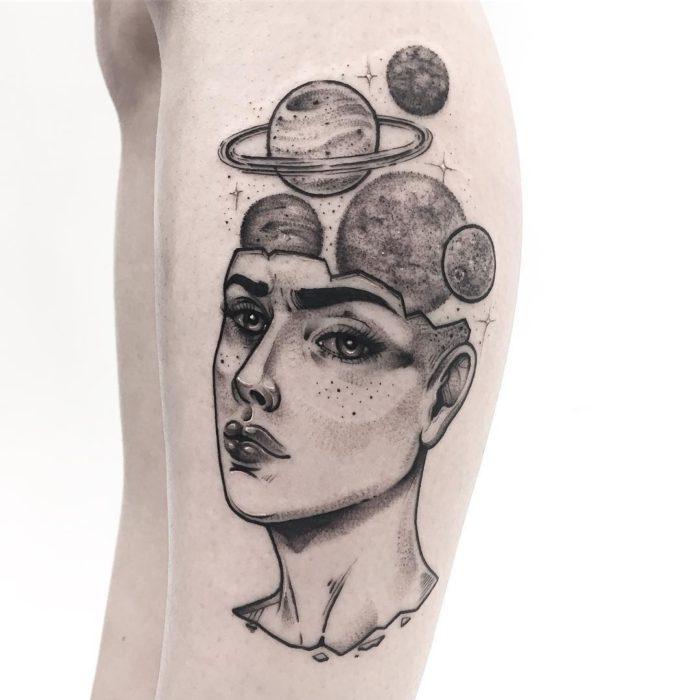Tatuaje de la cabeza de una mujer con planetas saliendo de su craneo