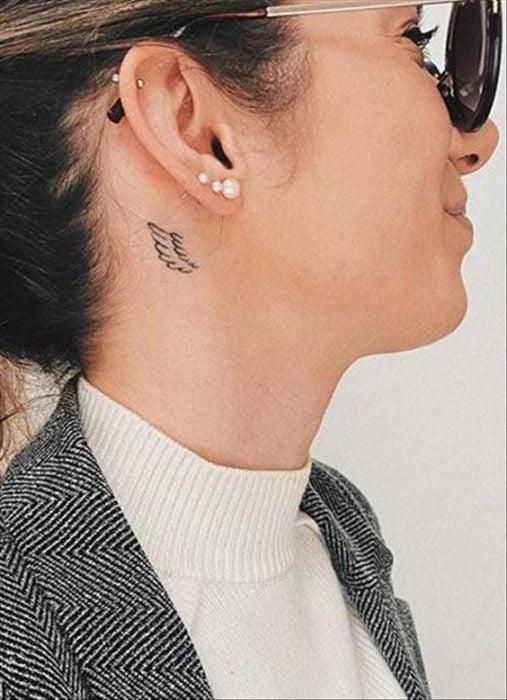 Tatuaje de ala en el cuello de mujer