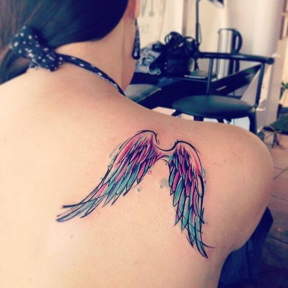 Tatuaje de alas con color rosa y morado en omóplatos de mujer