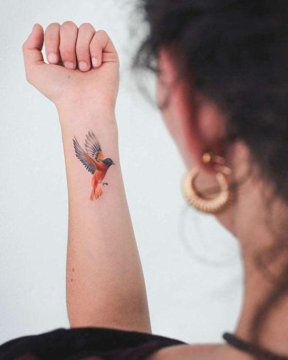Tatuaje de ave en muñeca izquierda de mujer