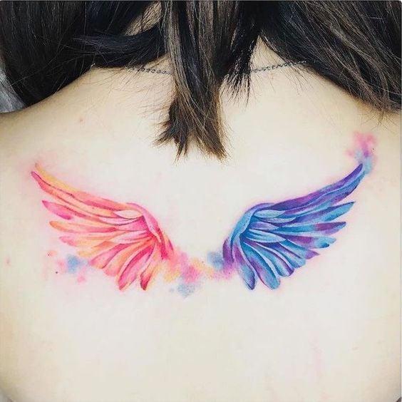 Tatuajes de alas coloridas en espalda de mujer