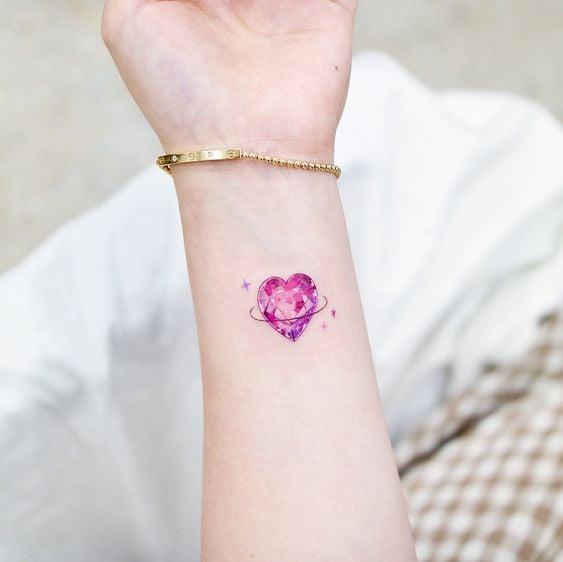 Tatuaje de corazón tipo piedra preciosa en la muñeca
