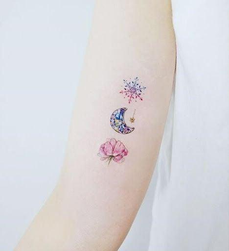Tatuaje de copo de nieve, luna y árbol estilo acuarela en el brazo