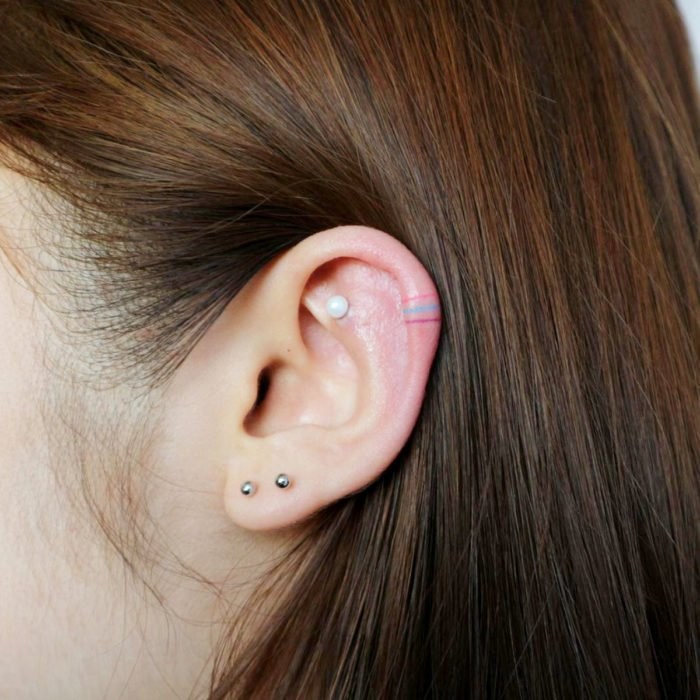 Tatuajes pequeños; minitatuaje de líneas de colores en la oreja, perforaciones