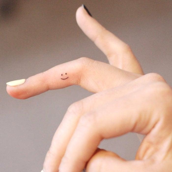 Tatuajes pequeños; minitatuaje de carita feliz en el dedo