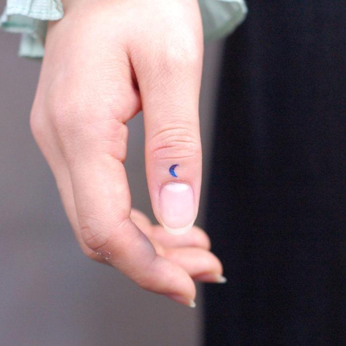 Tatuajes pequeños; minitatuaje de luna azul en el dedo pulgar