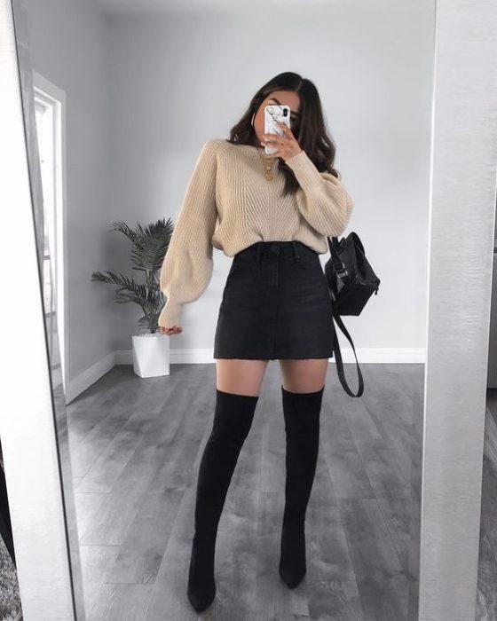 Chica se toma selfie frente al espejo con suéter beige, falda negra circular y botas altas negras