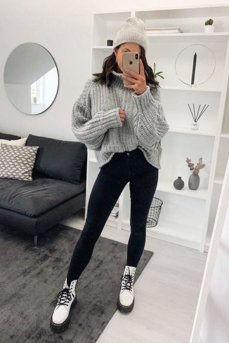 Chica de melena media se toma selfie frente al espejo con suéter gris oversized, pantalón negro y botas dr. martens blancas