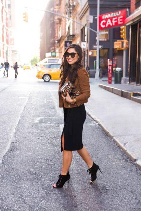 Mujer cruza la calle con gafas de sol negras, saco café, falda de lápiz negra y botines de tacón de aguja negros