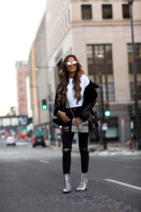 Chica de cabello largo castaño ondulado parada en la calle con pantalón y chamarra negros, blusa blanca y botines de animal print