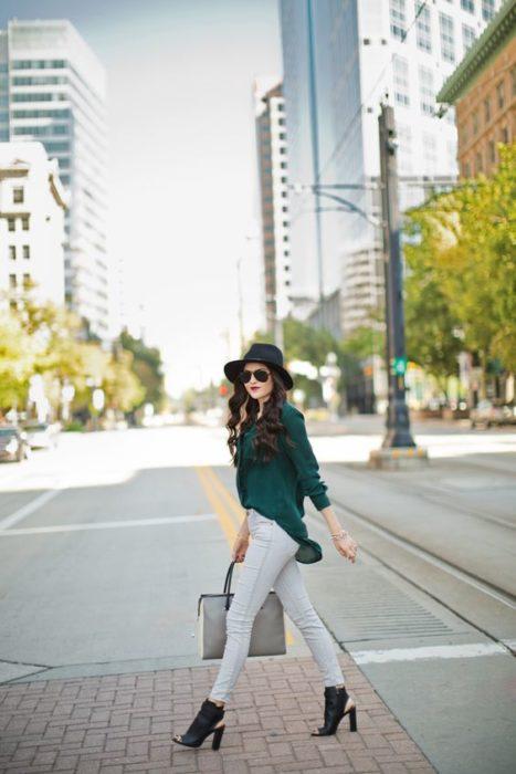 Chica elegante atraviesa la cale con pantalones de mezclilla claros, blusa verde esmeralda, sombrero negro y botines con abertura en la parte de adelante
