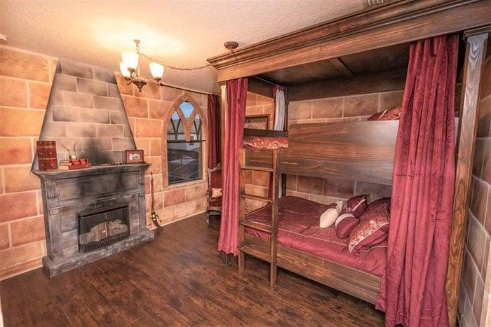 Habitación decorada con papel tapiz de ladrillos naranjas y cobijas en tonos color vino