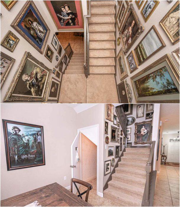 Pasillo con escaleras decoradas con cuadros antiguos y posters de Harry Potter