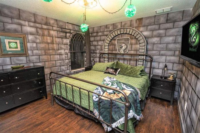 Habitación decorada con papel tapíz en forma de ladrillos grises con cobijas verdes